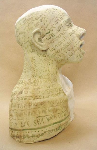 Singing Griot - Sculpture, ©2010 by Juarez Hawkins -                                                                                                                                                      Singing bust, painted with inscriptions on the left side, blank on the right side.
