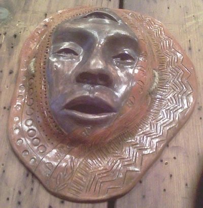 Relic - Sculpture, ©2010 by Juarez Hawkins -                                                                                                          Carved mask of a face, surrounded by stamping and carved designs